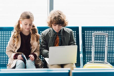 Photo pour Enfants regardant l'ordinateur portatif et s'asseyant sur des sièges bleus dans le hall d'attente dans l'aéroport - image libre de droit