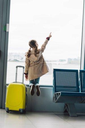 Foto de Vista trasera del niño preadolescente cerca de la maleta apuntando con el dedo en la ventana en la sala de espera en el aeropuerto - Imagen libre de derechos