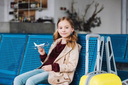 Photo for Preteen kid holding toy plane in airport departure lounge and looking at camera - Royalty Free Image
