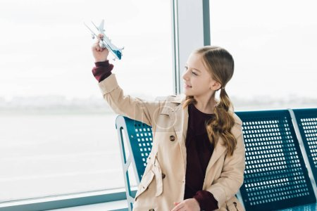 Photo for Smiling preteen kid holding toy plane in airport departure lounge - Royalty Free Image