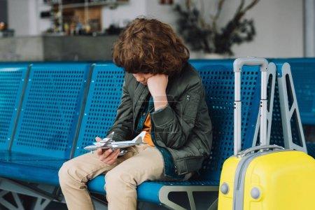 Photo pour Garçon de préadolescence retenant l'avion de jouet tout en s'asseyant dans le salon de départ d'aéroport - image libre de droit