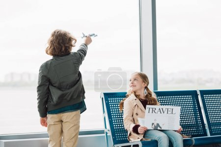 Photo for Cute preteen kid sitting in waiting hall with travel newspaper while boy playing with toy plane - Royalty Free Image