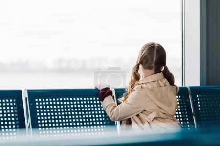 Photo for Back view of preteen kid looking at window in departure lounge - Royalty Free Image
