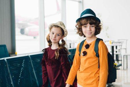 Photo pour Enfants adorables de préadolescence dans des chapeaux regardant l'appareil-photo dans la salle d'attente - image libre de droit