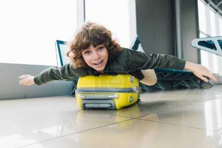 Photo for Excited preteen kid lying on suitcase with outstretched hands in airport departure lounge - Royalty Free Image