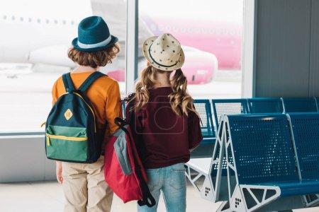 Foto de Vista trasera de los niños preadolescentes con mochilas en la sala de espera - Imagen libre de derechos