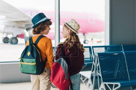 Foto de Vista trasera de los niños preadolescentes con mochilas en la sala de espera mirándose unos a otros - Imagen libre de derechos