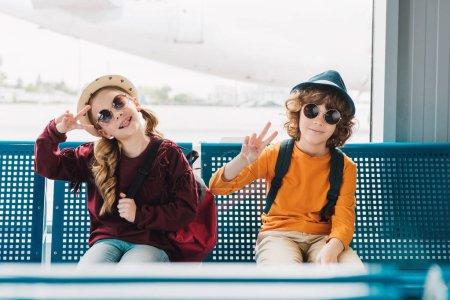 Photo pour Enfants de préadolescence dans des lunettes de soleil s'asseyant dans la salle d'attente et affichant des signes de paix - image libre de droit
