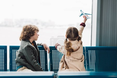 Photo for Cute preteen kids sitting in waiting hall and playing with toy plane - Royalty Free Image