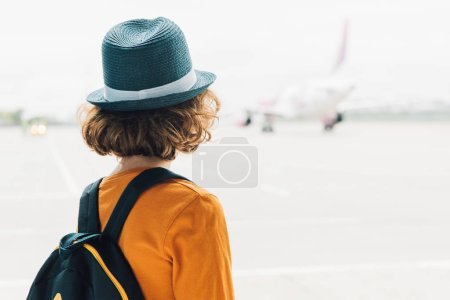 Photo for Back view of preteen kid with backpack in airport looking at plane through window - Royalty Free Image