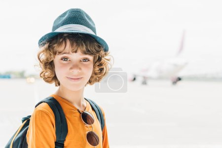 Photo for Adorable preteen kid in hat looking at camera in airport with copy space - Royalty Free Image