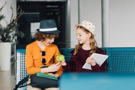 Photo pour Enfants mignons de préadolescence s'asseyant dans la salle d'attente et partageant la pomme - image libre de droit