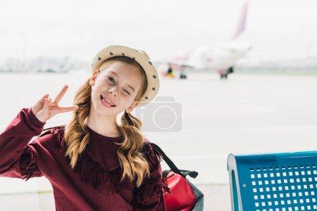 Photo pour Enfant mignon de préadolescence collant dehors la langue et affichant le signe de paix à l'aéroport - image libre de droit