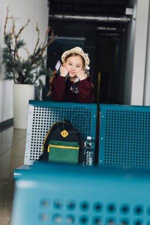 Photo pour Enfant adorable préadolescent avec passeport et billet d'avion dans la salle d'attente - image libre de droit
