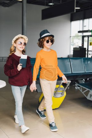 Photo for Preteen children in sunglasses with baggage and passport in waiting hall - Royalty Free Image