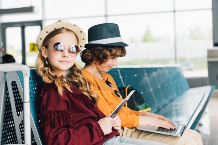 Photo for Cute preteen kids sitting in waiting hall with laptop and passport - Royalty Free Image
