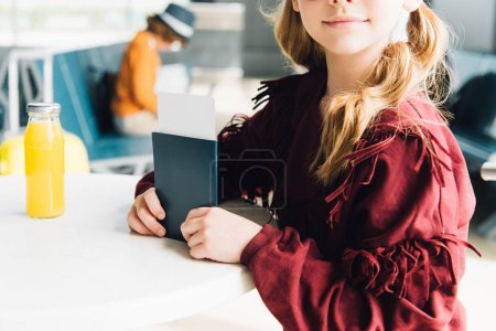 Photo for Partial view of preteen kid with passport and air ticket in airport - Royalty Free Image