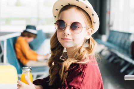 Photo pour Enfant de préadolescence mignon dans des lunettes de soleil se reposant avec le jus d'orange dans la salle d'attente - image libre de droit