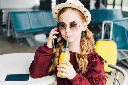 Photo pour Enfant de préadolescence buvant le jus d'orange et parlant sur le smartphone dans la salle d'attente - image libre de droit