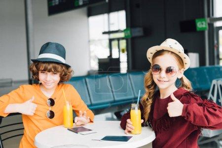 Photo pour Enfants de préadolescence s'asseyant à la table avec le jus d'orange dans le salon de départ et affichant des pouces vers le haut - image libre de droit