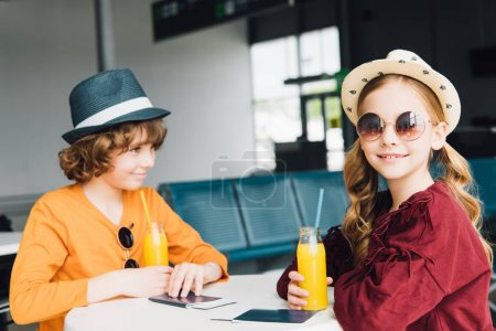 Photo for Preteen kids sitting at table with orange juice in departure lounge - Royalty Free Image