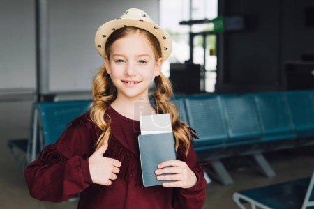 Photo pour Enfant de préadolescence mignon avec le passeport et le billet d'avion affichant le pouce vers le haut dans l'aéroport - image libre de droit