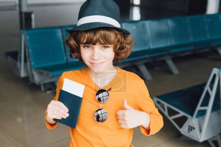 Photo for Cute boy with passport and air ticket showing thumb up in airport - Royalty Free Image