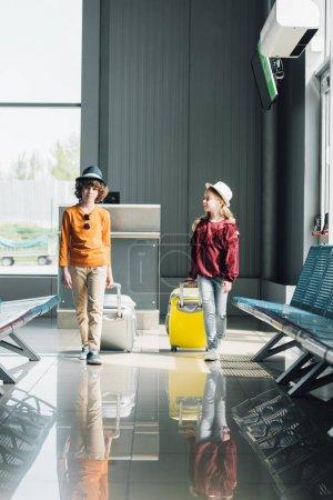 Photo pour Adorables enfants préadolescents avec des valises dans le hall d'attente à l'aéroport - image libre de droit