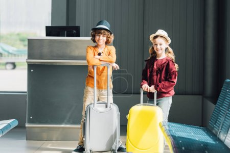 Photo for Adorable preteen kids with suitcases in waiting hall looking at camera - Royalty Free Image