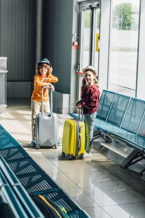 Photo pour Enfants adorables de préadolescence avec des valises dans le hall d'attente regardant l'appareil-photo - image libre de droit
