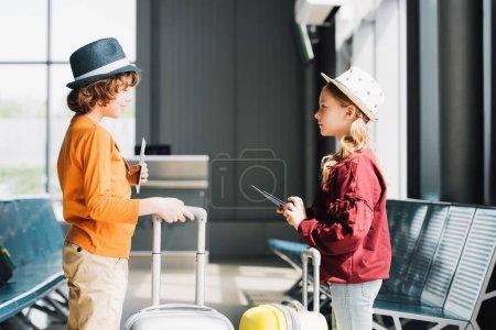 Photo pour Préadolescents avec valises, billets d'avion et passeports dans la salle d'attente - image libre de droit