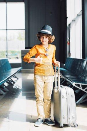 Photo pour Garçon de préadolescence avec la valise affichant le pouce vers le haut dans le hall d'attente dans l'aéroport - image libre de droit