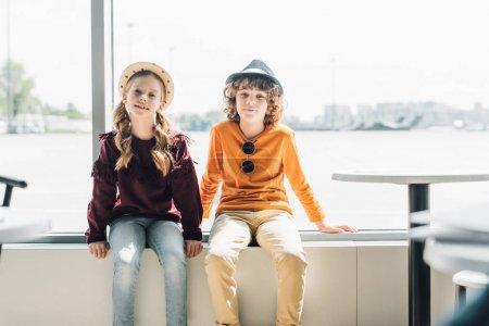 Foto de Adorables niños preadolescentes sentados en la ventana durante el día y mirando a la cámara - Imagen libre de derechos