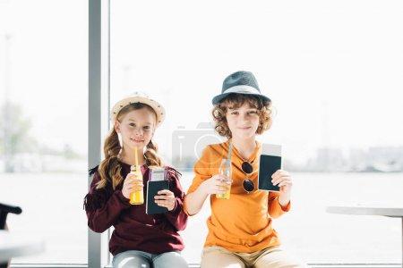Photo pour Enfants mignons de préadolescence dans le hall d'attente à l'aéroport avec des passeports, des billets d'avion et du jus d'orange - image libre de droit
