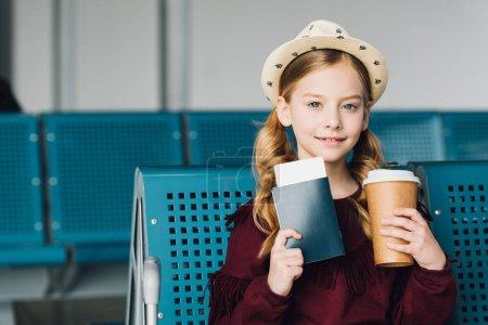 Photo pour Enfant de préadolescent souriant avec le passeport, le café pour aller et le billet d'avion à l'aéroport - image libre de droit