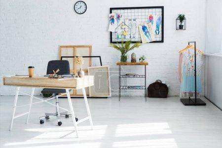 Photo pour Tasse en papier et stationnaire sur la table en bois près des croquis de mode avec des notes collantes - image libre de droit