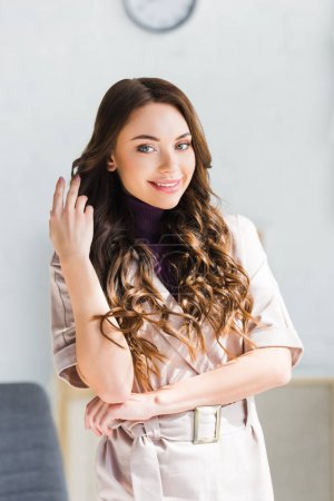 Photo for Cheerful young woman looking at camera while touching hair - Royalty Free Image