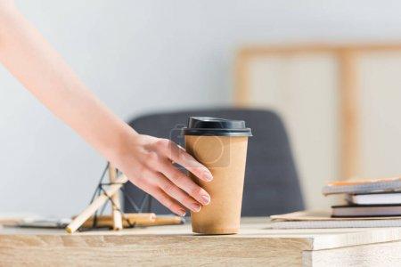 Ausgeschnittene Ansicht einer Frau, die Kaffee in der Nähe von Schreibwaren und Notizbüchern hält
