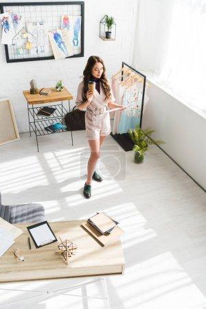Foto de Vista aérea de diseñador rizado mirando bocetos de moda mientras sostiene la taza de papel - Imagen libre de derechos