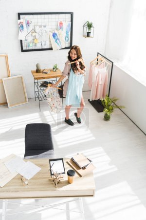 Foto de Vista aérea de la mujer alegre sosteniendo ropa en el estudio de diseño - Imagen libre de derechos
