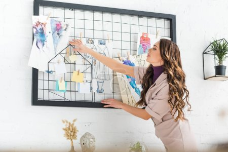 Photo for Selective focus of curly girl standing and touching white board with fashion sketch - Royalty Free Image