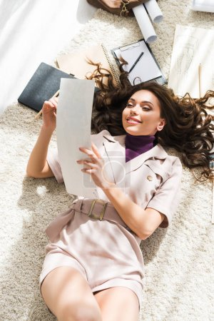Photo for Top view of cheerful woman lying on carpet and looking at blank paper - Royalty Free Image
