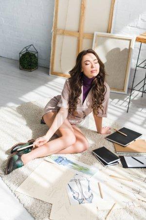 Photo pour Concepteur bouclé attrayant s'asseyant sur le tapis avec les yeux fermés - image libre de droit