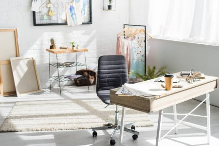 Photo pour Tasse en papier et stationnaire sur la table près des vêtements et des croquis de mode - image libre de droit