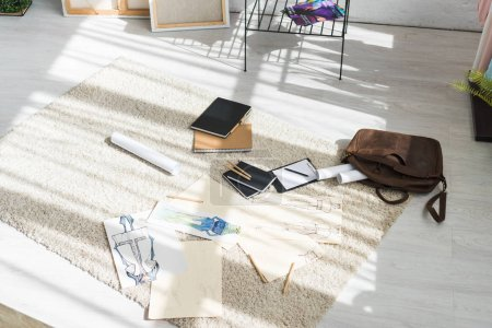 notebooks and fashion sketches on carpet near bag and clipboard