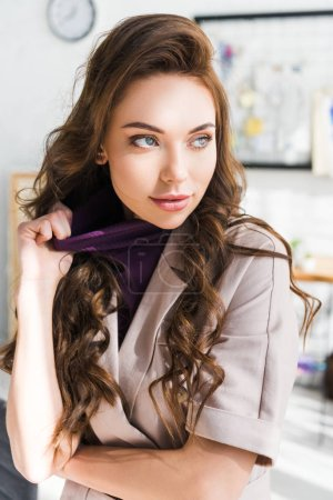 Photo for Attractive curly young woman touching clothing in design studio - Royalty Free Image