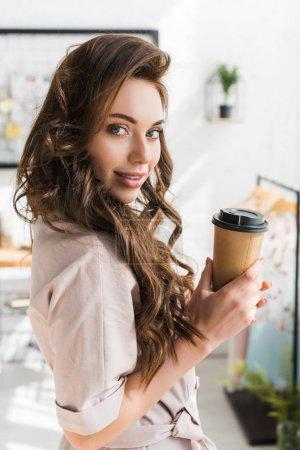Photo pour Belle jeune femme regardant l'appareil-photo tout en retenant la tasse jetable - image libre de droit