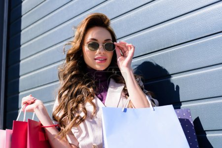Photo pour Jeune femme bouclée gaie touchant des lunettes de soleil tout en retenant des sacs à provisions - image libre de droit