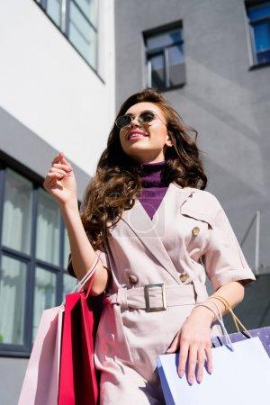 Photo pour Vue d'angle bas de jeune femme bouclée positive dans des lunettes de soleil restant avec le sac à provisions - image libre de droit