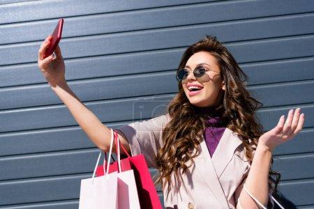 Photo pour Heureuse femme bouclée avec des sacs à provisions prendre selfie sur smartphone - image libre de droit